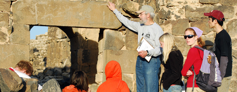 Main image: Project director Bert de Vries discusses lintel inscriptions with a group of international students during a tour through Umm el-Jimal.