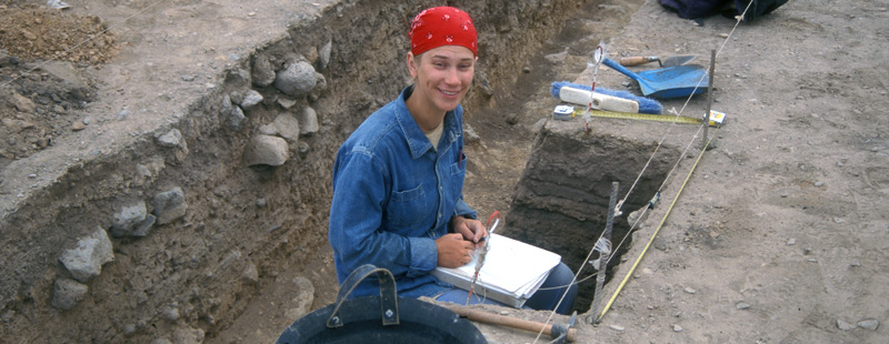 Main image: A square supervisor writes excavation field notes inside her trench.