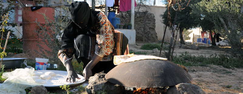 Main image: A local woman prepares fresh dough while baking bread over a fire in front of her home near Umm el-Jimal's ruins.