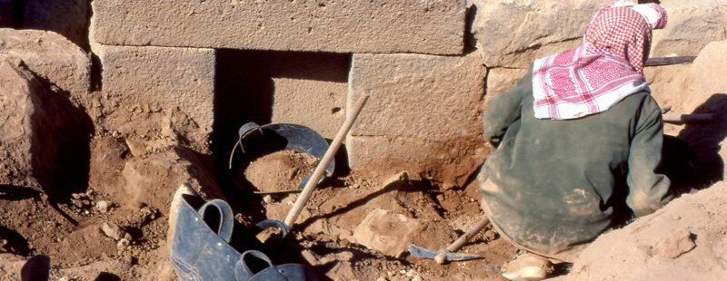 Main image: A researcher examines basalt stonework inside an excavation trench exposing a building foundation.